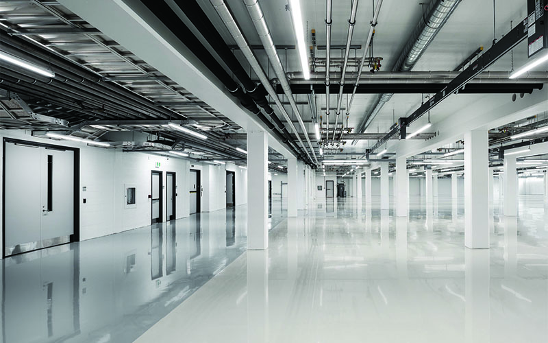 Starlim, open concept empty warehouse area, white flooring, walls with industrial pipes along the ceiling.